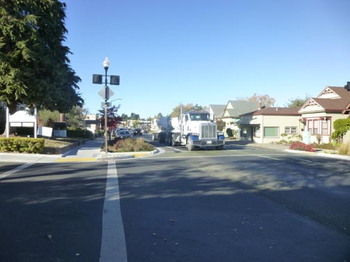 An improved crosswalk. Bump-outs and flashing crossing signal improve safety, but Main Street still often feels like a highway rather than a small town main street.